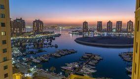 Evening at the Pearl-Qatar day to night timelapse from top. It is an artificial island in Qatar. View of the Marina and residential buildings in Porto Arabia stock video footage