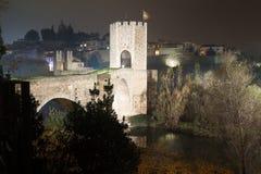 Evening photo of Medieval bridge with city gate. Besalu, Catalon. Evening photo of illumination of medieval town on banks of river. Besalu, Catalonia royalty free stock photo