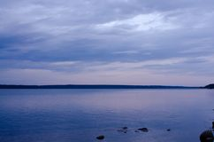 Wide waterscape against cloudy sky Stock Images