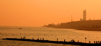 Evening on the Pier Panoramic. People fishing on a pier with the sea in the background in the orange light of the late afternoon in Spain Royalty Free Stock Photo