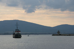 Evening port - 1. Fishing ship enters the port in the evening on a background of mountains Stock Photo
