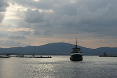 Evening port - 2. Fishing ship enters the port in the evening on a background of mountains Stock Image