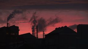 Evening at power station red sky silhouette smoke comes out of chimney. Power station in the evening as smoke goes into the sky stock video footage