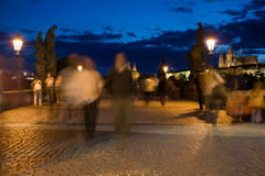 Evening Prague scenery. People walking on Charles Bridge with Little Quarter on the background Royalty Free Stock Photo