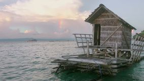 Evening rainbow and floating hut. Indonesia. Evening on the shore of a tropical island. Amazing clouds and a piece of rainbow. Hut on the raft in the foreground stock footage