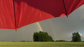 Evening rainbow over  fields and red umbrella motion. Evening rainbow over farmland fields and red umbrella motion stock footage