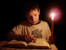 Evening reading. Reading at a candle royalty free stock image