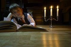 Evening reading. The boy reading the book in the candlelight stock image