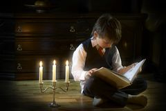 Evening reading. The boy reading the book in the candlelight Royalty Free Stock Image