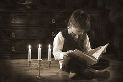 Evening reading. Retro styled image with the boy reading the book in the candlelight Stock Photos