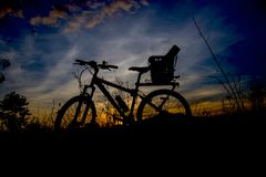 Evening recreation with bicycle with sunset and dramatic sky. Stock Photos