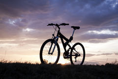 Evening recreation with bicycle. With sunset and dramatic sky Royalty Free Stock Photos