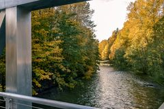 Dark river in autum. Evening river flowing under metallic bridge with autumn colored leaves on maples surrounding Stock Image