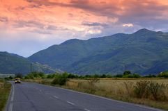 Evening road to mountains Stock Images