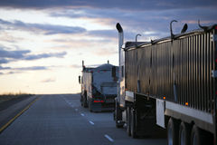 Evening road uphill with convoy semi trucks with bulk trailers. Several semi trucks with bulk cargo trailers move by convoy on the road towards of the evening royalty free stock photography