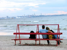 Evening romance. Couple sitting and chatting on a beach bench. City of Tallinn in the distance Stock Image
