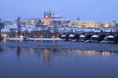 Evening romantic colorful snowy Prague gothic Castle with Charles Bridge Stock Photo