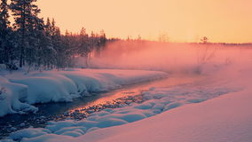 Evening Rose Mist over the Snow-Covered Forest and a River. Lapland. Winter forest. All covered with a thick layer of snow. The last colours of the sunset and stock footage