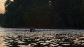 Evening rowing at kayak on the river canal on the urban landscape background. Evening rowing on kayak at the river canal on the high-rise buildings background stock video footage