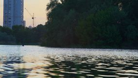 Evening Rowing on Kayak at the River Canal on the High-Rise Buildings Background. Evening Rowing at Kayak on the River Canal on the Urban Landscape Background stock video