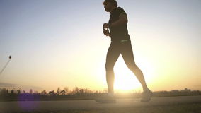 Evening runner drinks water on the wide angle sunset landscape stock footage