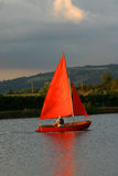 Evening sail. Mature man sailing his boat in th evening sun Stock Photo