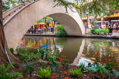 Evening San Antonio River Walk Bridge. SAN ANTONIO, TEXAS - SEPT 20, 2014: Bridge over San Antonio River with tourists dining, strolling, and shopping in stock photography