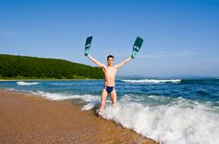 Evening on the sea. The young man holds in hands sports flippers Stock Image