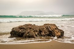 Evening sea behind a shoreline rock Royalty Free Stock Images