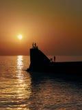 Evening sea. Orange sunset silhouettes of bathers Stock Images