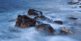 Evening sea with rocks long exposure. Stock Photo