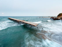 Evening sea surf, ruined pier and Moon in sky (Black Sea, Bulgar Royalty Free Stock Images