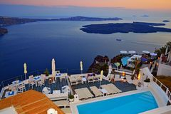 Luxury outdoor pool deck overlooking Santorini island Caldera Greece. Evening sea view from luxurious holiday villa outdoor pool deck perched on the top of Stock Images