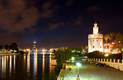 Evening in Seville. The pleasant evening walk along Guadalquivir river, enjoying such landmarks as Puente de Triana (Triana Bridge) and Torre del Oro in the stock image