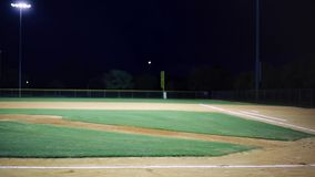 Evening shot of empty baseball field.  Some lightning in the sky. stock video