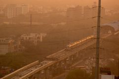 Evening shot of metro train on foggy delhi day. This is shot through electric wires that feed power to the railway lines. The metro is a power efficient public Stock Image