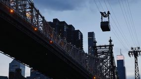 Evening Shot of Roosevelt Island Tram Next to Queensboro Bridge. A dusk establishing shot of the Roosevelt Island Tram carrying passengers next to the Ed Koch stock video footage