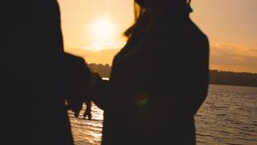 Evening silhouette of lovely couple, stands at the lake with sunset glow. Man kisses female hands. Close-up. Slowly stock footage
