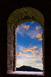 Evening clouds ancient stone wimdow Stock Images