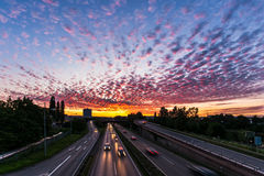 Evening sky. Cars drive home in evening traffic as the sun sets Stock Photo