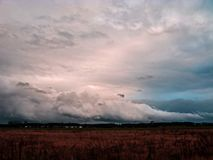 Dark, sinister clouds over the plain. Evening sky covered with a layer of dark, ominous, rainy clouds. It`s evening. Sunlight turns red. The bottom is covered royalty free stock image