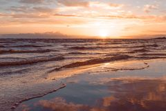 Evening sky reflected in water on sand as in a mirror in the background sea in blur Royalty Free Stock Images