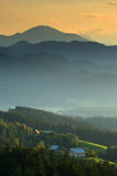 Evening in Slovenian hills. A small farm in front Stock Photos