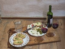 evening snack - plates with cutted chees, salami, olives,tomatos, herb butter bagels and red wine bottle with two glasses and st royalty free stock photography