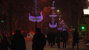 Evening snow-covered town in the Christmas illuminations in the   heavy snow. stock video