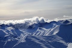Evening snowy mountains in mist and sunlight clouds Royalty Free Stock Photography