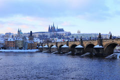 Evening snowy Prague gothic Castle with Charles Bridge, Czech Republic Royalty Free Stock Images