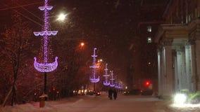 Evening snowy street in a festive Christmas illuminations in heavy   snow. stock footage