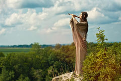 Evening Song elf. Girl in period costume playing the flute at the edge of the cliff Stock Photo