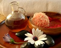 Evening spa set up. Evening spa preparations with massage oil, floral scented water, stones and towel Stock Photo